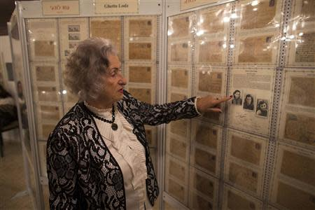 Jewish Holocaust survivor Wodzislawski points to pictures displayed at a museum inside her home in Ariel