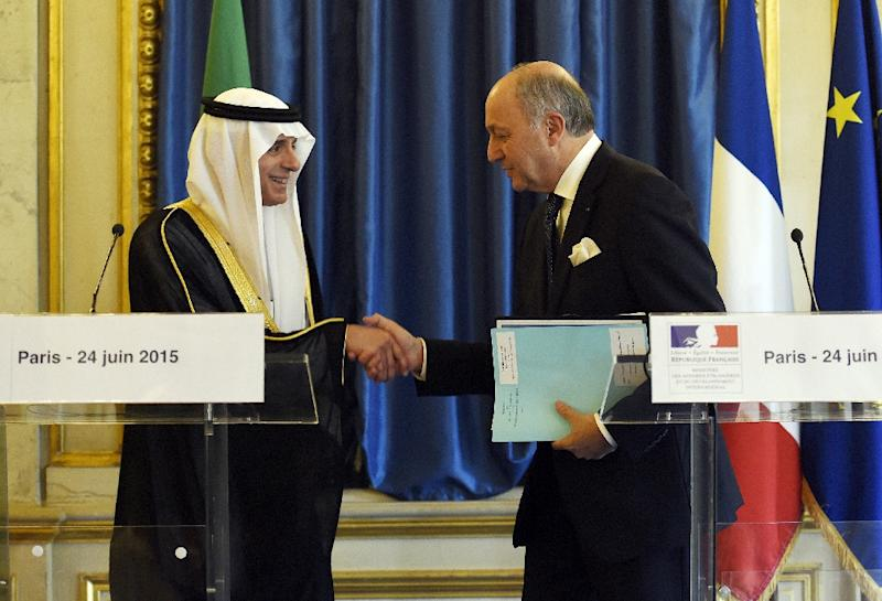 French Foreign Minister Laurent Fabius (right) shakes hands with Saudi Defence Minister Prince Mohamed bin Salman after a press conference in Paris on June 24, 2015