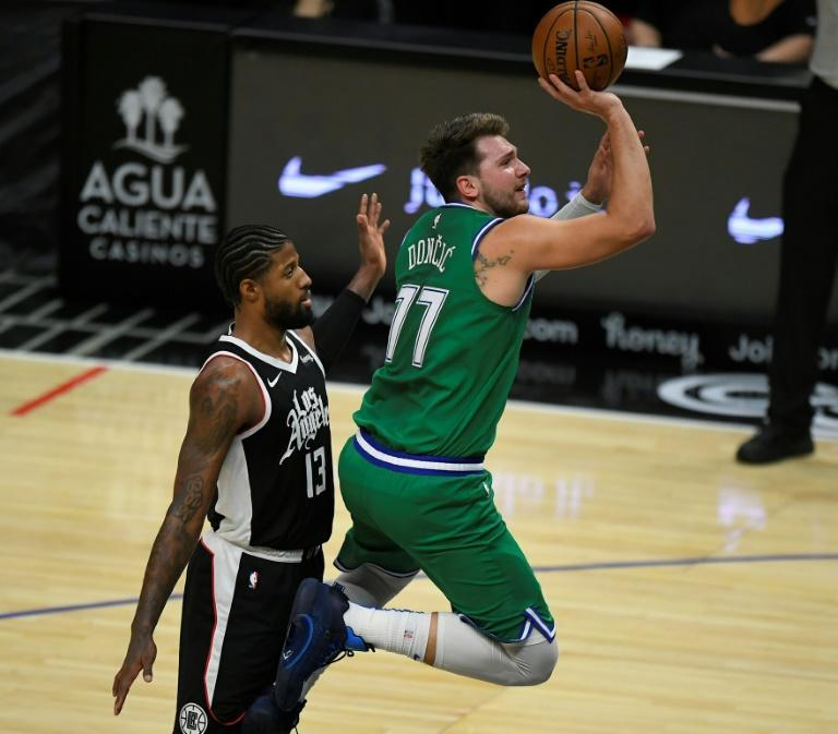 Paul George of the LA Clippers fouls Luka Doncic of Dallas as he drives to the basket in the Mavericks' 124-73 NBA victory over the Clippers