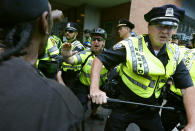 """FILE - In this Aug. 19, 2017, file photo, counterprotesters clash with police following a """"Free Speech"""" rally staged by conservative activists in Boston. Boston's police department remains largely white in 2021, despite vows for years by city leaders to work toward making the police force look more like the community it serves. (AP Photo/Michael Dwyer, File)"""