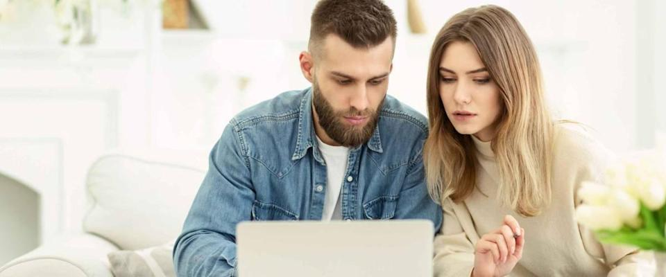 Millennial couple manage expenses with laptop and check accounts and invoices, panorama