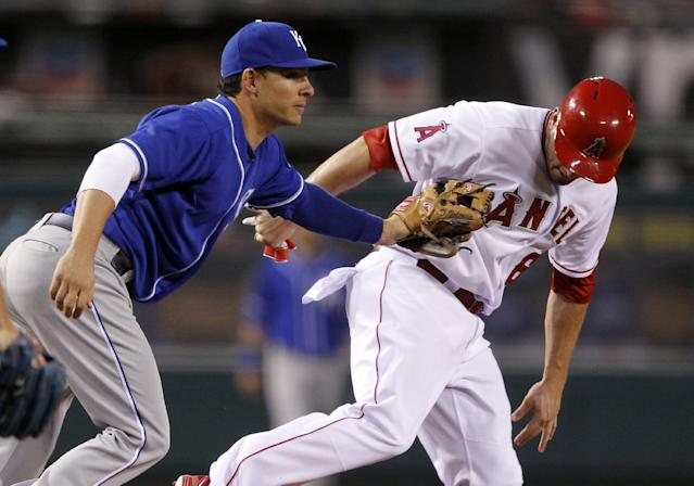 Kansas City Royals third baseman Danny Valencia, left, tags out Los Angeles Angels' David Freese in a rundown between third and second base, on a fielder's choice to the pitcher by Angel's Erick Aybar, in the 10th inning of a baseball game Saturday, May 24, 2014, in Anaheim, Calif. (AP Photo/Alex Gallardo)
