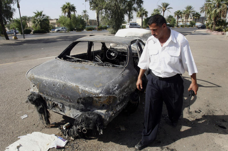 FILE - In this Sept. 25, 2007 file photo, an Iraqi traffic policeman inspects a car destroyed by a Blackwater security detail in al-Nisoor Square in Baghdad, Iraq. The U.S. Justice Department has brought fresh charges against former Blackwater Worldwide security contractors over a deadly 2007 shooting on the streets of Baghdad. The jury indictment announced Thursday, Oct. 17, 2013 charges four men with voluntary manslaughter and other crimes. The case stems from the shooting of 17 Iraqi civilians. Blackwater security contractors were guarding U.S. diplomats when they opened fire at an intersection. Their lawyers have said the insurgents ambushed the guards. (AP Photo/Khalid Mohammed, File)