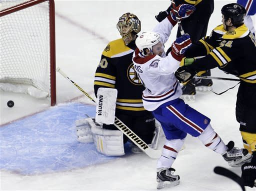 Boston Bruins goalie Tuukka Rask (40), of Finland, left, watches as the puck flies into the net while Boston Bruins defenseman Adam McQuaid (54), right, shoves Montreal Canadiens center David Desharnais (51), second from left, in the third period of an NHL hockey game at the TD Garden, in Boston, Sunday, March 3, 2013. The goal was scored by Canadiens left wing Max Pacioretty, not shown, to tie the game. The Canadiens beat the Bruins 4-3. (AP Photo/Steven Senne)