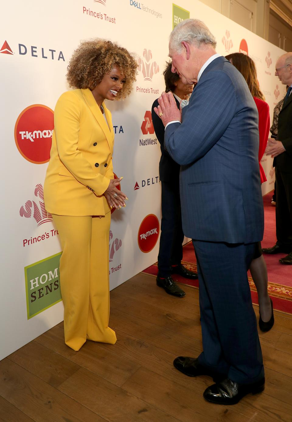 The Prince of Wales uses the Namaste gesture to greet Fleur East as he arrives at the annual Prince's Trust Awards 2020 held at the London Palladium.