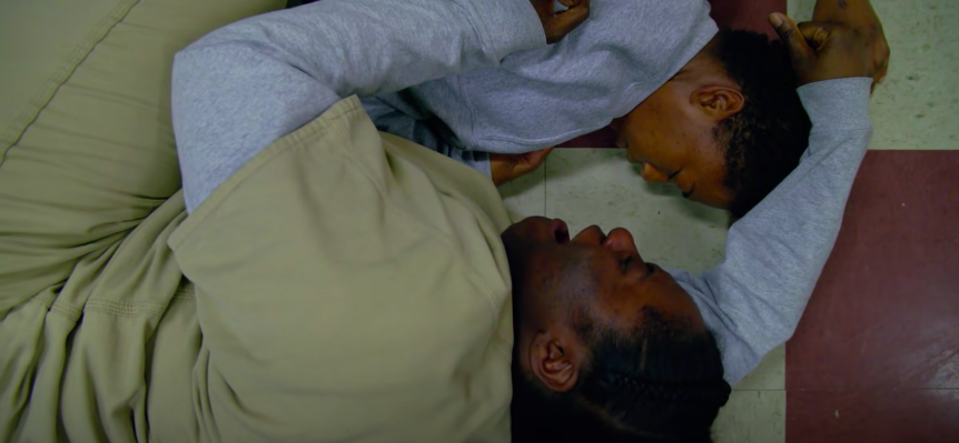 Poussey on the floor as another inmate holds her body