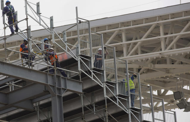 Men work at the Itaquerao stadium in Sao Paulo, Brazil, Wednesday, April 9, 2014. The stadium which remains under construction is slated to host the World Cup opener match between Brazil and Croatia on June 12. About 20,000 temporary seats are being installed behind the goals to increase the stadium's capacity to nearly 70,000. (AP Photo/Andre Penner)