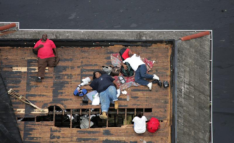 Residents wait on a roof top to be rescued from the floodwaters of Hurricane Katrina