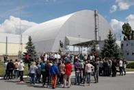 Visitors stand outside the New Safe Confinement (NSC) structure over the old sarcophagus covering the damaged fourth reactor at the Chernobyl Nuclear Power Plant, in Chernobyl