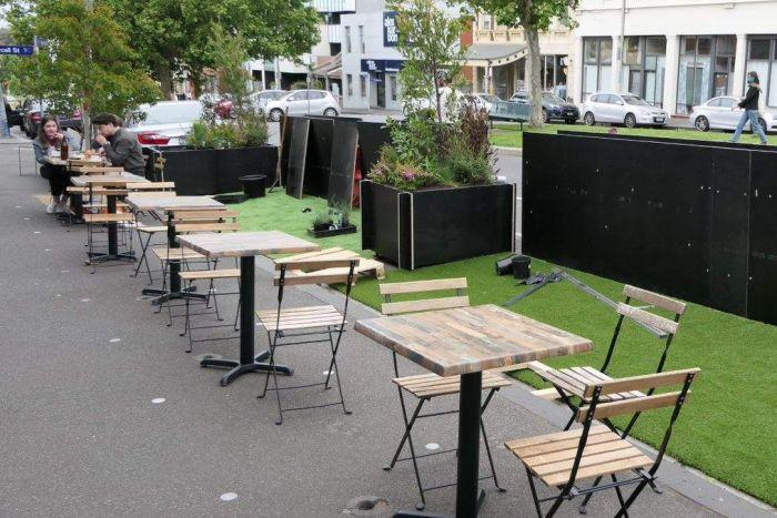 A row of distanced tables and chairs line the footpath outside a cafe in Melbourne.