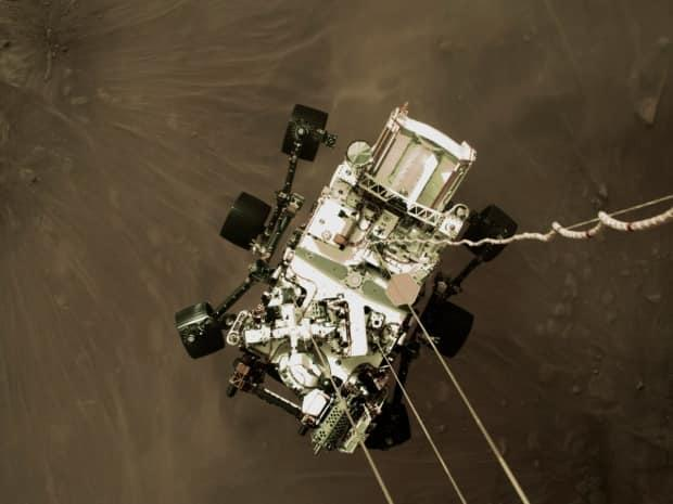 This Thursday, Feb. 18, 2021, photo provided by NASA shows the Perseverance rover lowered toward the surface of Mars during its powered descent.