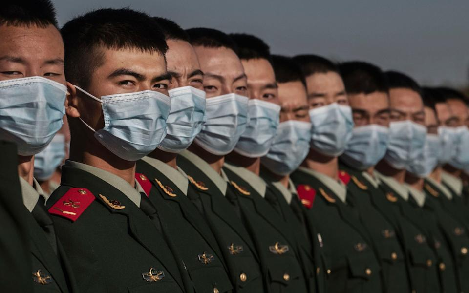 Chinese soldiers from the People's Liberation Army wear protective masks as they line up after a ceremony marking the 70th anniversary of China's entry into the Korean War - Getty Images Asia