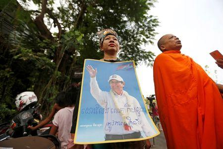 Supporters of Kem Sokha, former opposition leader and ex-president of the now-dissolved Cambodia National Rescue Party (CNRP), hold up a poster near the Appeal Court in Phnom Penh, Cambodia