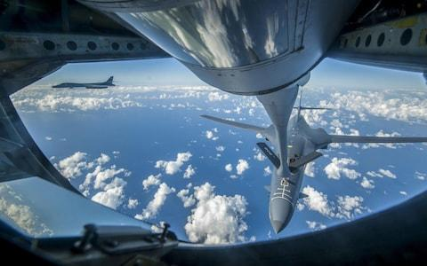 An Air Force B-1B Lancer receives fuel from a KC-135 Stratotanker near the East China Sea - Credit: AFP