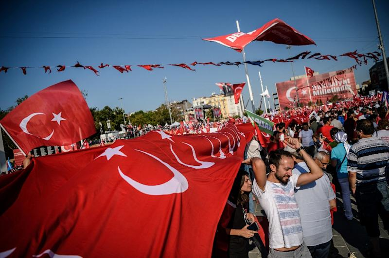 Demostrators hold a giant Turkish national flag at Istanbul's Taksim Square on July 24, 2016 during a cross-party rally