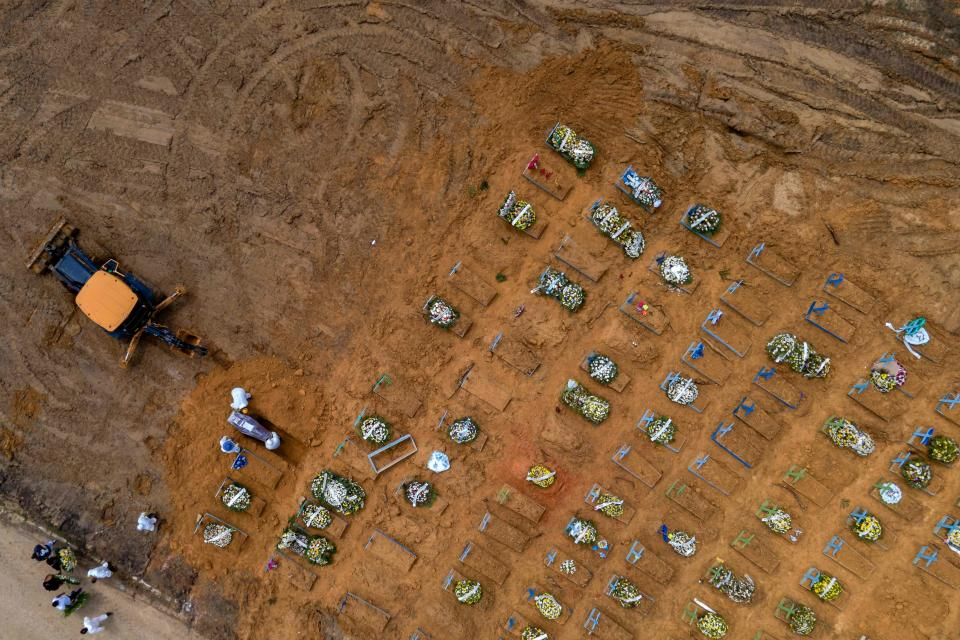 Aerial view showing a tractor digging graves in a new area of the Nossa Senhora Aparecida, where COVID-19 victims are buried, in Manaus, Brazil, on January 22, 2021. - With over 3,000 burials in January, the COVID-19 pandemic accelerates the expansion of the largest cemetery in the capital of Amazonas state. (Photo by MARCIO JAMES / AFP) (Photo by MARCIO JAMES/AFP via Getty Images)