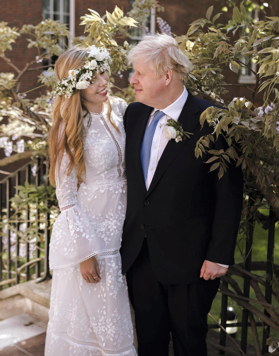 In this image released Sunday May 30, 2021, by Downing Street, Britain's Prime Minister Boris Johnson and Carrie Johnson pose together for a photo in the garden of 10 Downing Street after their wedding on Saturday. Boris Johnson and his fiancée Carrie Symonds are newlyweds, according to an announcement from his Downing Street office saying they were married Saturday May 29, in a small private ceremony in London. (Rebecca Fulton/Downing Street via AP)