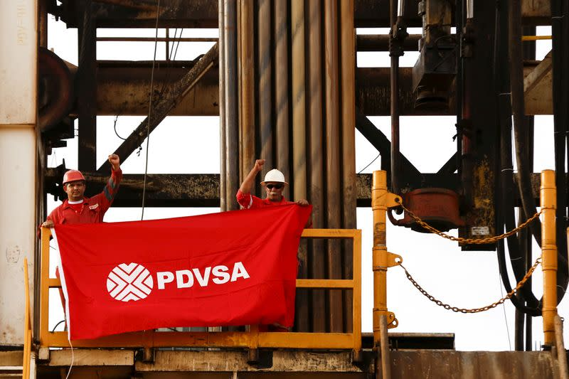 FILE PHOTO: Oilfield workers hold a flag with the corporate logo of Venezuela's state oil company PDVSA, in a drilling rig at an oil well operated by them, in the oil rich Orinoco belt, near Cabrutica at the state of Anzoategui