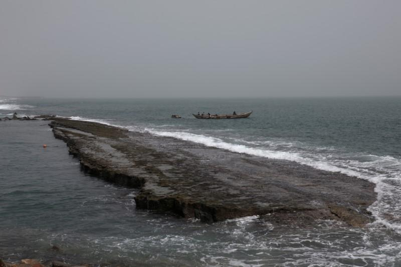 A boat passes by the remains of a costal road that has fallen into the sea due to coastal erosion in Lome