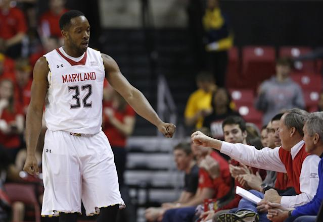 FILE- In this March 4, 2014, file photo, Maryland's Dez Wells (32) fist-bumps a fan in the second half of an NCAA college basketball game against Virginia Tech in College Park, Md. Wells, a former Xavier University basketball player, who was expelled over what he says was a false rape allegation has settled his lawsuit against the school over their handling of the case. Federal Judge S. Arthur Spiegel dismissed Wells' lawsuit against Xavier, Thursday, April 24, 2014, saying the two had resolved their conflict. (AP Photo/Patrick Semansky, File)