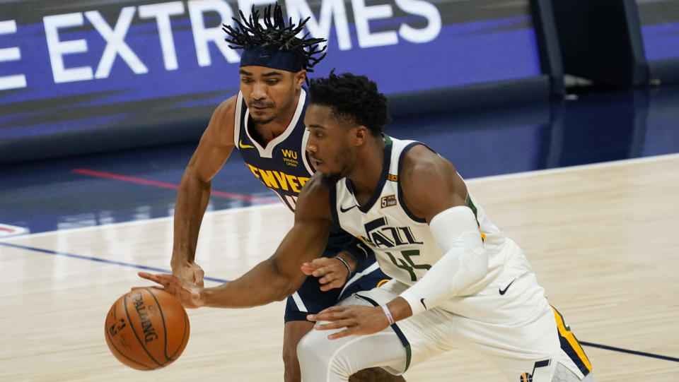 Utah Jazz guard Donovan Mitchell, front, pursues the ball with Denver Nuggets guard Gary Harris in the first half of an NBA basketball game Sunday, Jan. 17, 2021, in Denver. (AP Photo/David Zalubowski)