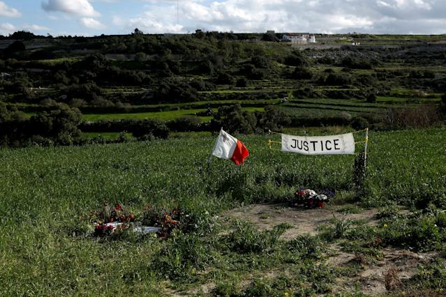 FILE PHOTO: A Maltese flag and banner calling for justice are seen at the scene of the assassination of anti-corruption journalist Daphne Caruana Galizia, one hundred days after her murder in a car bomb explosion, in Bidnija, Malta January 24, 2018. REUTERS/Darrin Zammit Lupi TPX IMAGES OF THE DAY/File Photo