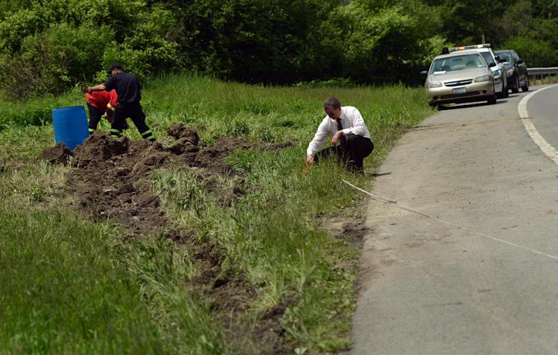 Cortland County Sheriff's Investigator, Shawn Conway, works the scene of a fatal car crash along Route 13 in Truxton, N.Y., Thursday, May 30, 2013. A minivan carrying two families was hit by a runaway trailer hauling crushed cars, killing four young children and three adults in their early 20s, authorities said Thursday. Cortland County Coroner Whitney Meeker told The Associated Press that all seven victims, including four children under 10, were local residents. They were killed and a man was injured when their van was hit by a trailer that broke away from a truck on Route 13 around 6 p.m. Wednesday in the rural town of Truxton, about 25 miles south of Syracuse. (AP Photo/Heather Ainsworth)