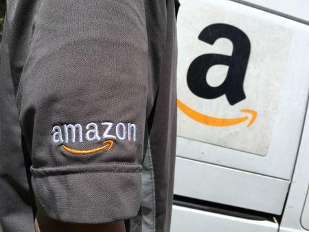 An Amazon.com Inc driver stands next to an Amazon delivery truck in Los Angeles