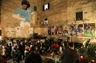 People gather at the top of the Quartieri Spagnoli in Naples by a 1990 mural representing Maradona, following the death of the Argentine on Wednesday