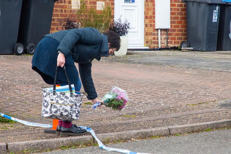 A neighbour leaves flowers near the family's home. (SWNS)
