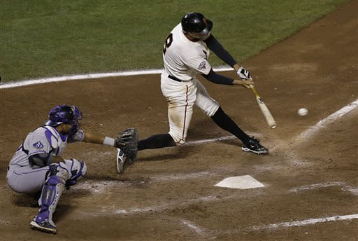San Francisco Giants' Hunter Pence (8) singles in front of Colorado Rockies catcher Wilin Rosario to score Nick Noonan during the sixth inning of a baseball game in San Francisco, Tuesday, April 9, 2013. (AP Photo/Jeff Chiu)