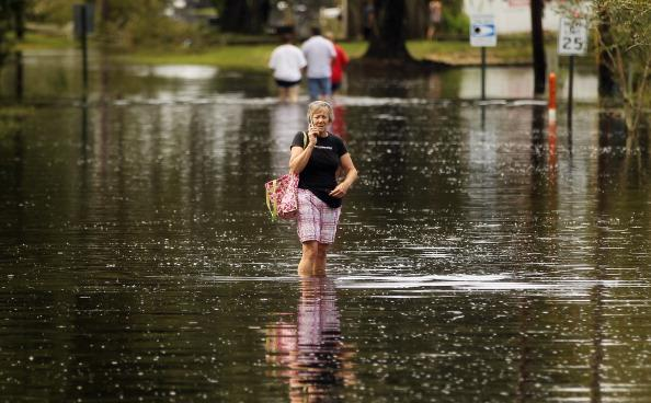A woman talks on her phone as she walks down a flooded street on August 31, 2012 in Slidell, Louisiana. Louisiana residents are coping with the aftermath of Hurricane Isaac with ongoing flooding, destroyed property and many still without electricity. (Photo by Mario Tama/Getty Images)