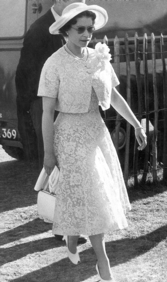 <p>Arriving at Windsor Palace for a garden party, the Queen was wearing a lemon lace two-piece teamed with a wide-rimmed hat and sunglasses. The perfect late 50s attire for a cocktail reception. <i>[Photo: Rex]</i></p>