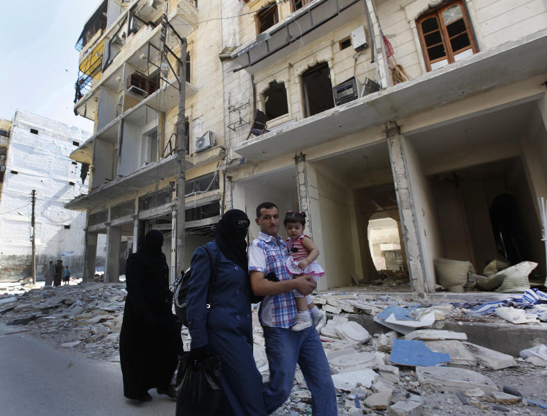 A Syrian family walk past a destroyed street that was attacked by a Syrian government airstrike earlier in the day at al-Shaar neighborhood, in Aleppo city, Syria, Monday Sept. 24, 2012. Syrian warplanes bombed two buildings on Monday in the northern city of Aleppo, killing at least five people including three children from the same family, activists said. (AP Photo/Hussein Malla)
