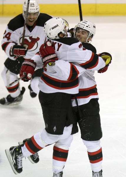 New Jersey Devils' Bryce Salvador, rear, and Marek Zidlicky, left, celebrate with Adam Henrique (14) after his goal in the second overtime against the Florida Panthers in Game 7 in a first-round NHL Stanley Cup playoff hockey series, in Sunrise, Fla., Wednesday, April 26, 2012. The Devils won 3-2. (AP Photo/J Pat Carter)