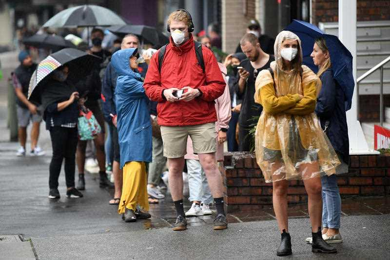 People are seen queuing outside a Centrelink office in Bondi Junction, Sydney.