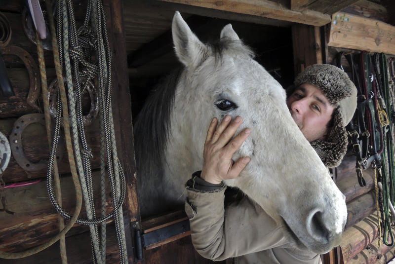 """In this photo taken on Tuesday, Feb. 12, 2013, Simion Craciun, a Romanian farmer, poses with a horse at Sieu Sfantu, in Romania's central region Transylvania. The name of his farm translates roughly as """"Saving Horses from Wolves."""" But for Simion Craciun, the real predators are from the nearby slaughterhouse. When word has gotten to him that a horse is being sold to the abattoir in the poor northern Transylvania region where he lives, he has rushed out to offer more money and bring the creature back to his picturesque plot where tourists come for riding lessons, he said. (AP Photo/Olimpiu Gheorghiu)"""