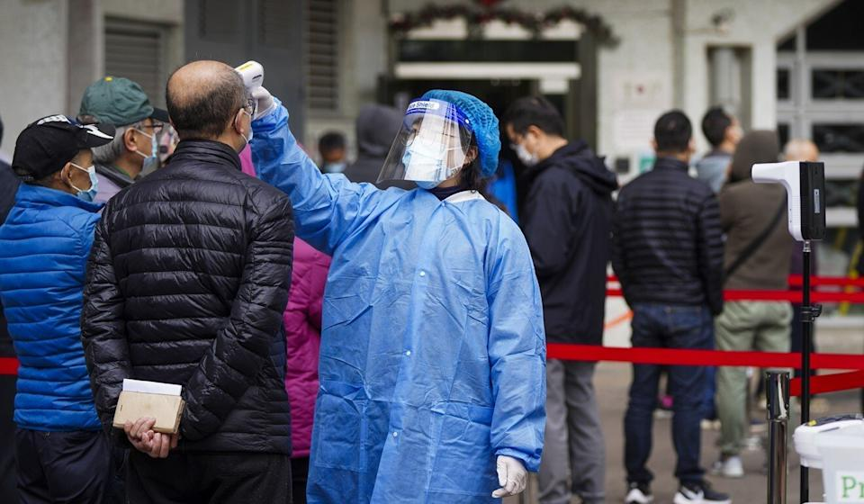 A medical staff member takes the temperature of residents as they queue up for Covid-19 testing at King Tsui Court in Chai Wan. Photo: Sam Tsang