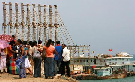 FILE PHOTO -  A group of Sri Lankan visitors at the new deep water shipping port watch Chinese dredging ships work in Hambantota