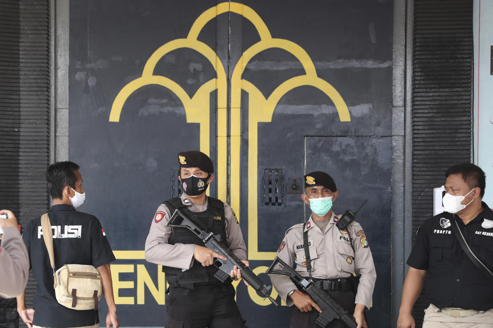 Police officers guard at the main entrance gate of Tangerang prison in Tangerang on the outskirts of Jakarta, Indonesia, Wednesday, Sept. 8, 2021. A massive fire raged through the overcrowded prison early Wednesday, killing a number of inmates. (AP Photo/Tatan Syuflana)