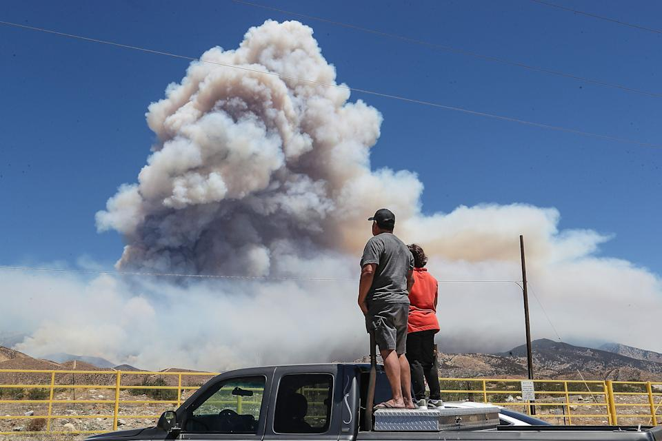 Brutencio and Marina Vidal watch as the Apple Fire burns in the foothills north of Cabazon, Calif., on August 7, 2020.  The Vidals are from nearby Banning.