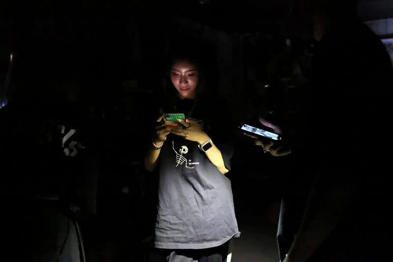 A woman uses her phone while experiencing a blackout due to an outage at a power plant, in Taipei