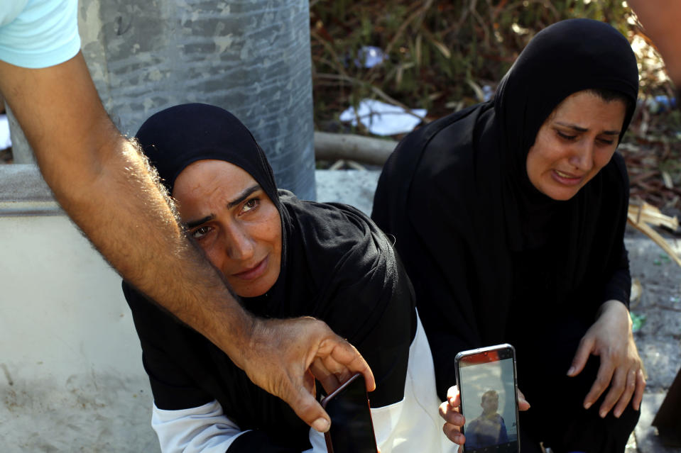 Zeinab Zer Eldin, left, and her sister-in-law shows a photo of her missing husband near the site of the explosion in the port of Beirut, Lebanon, Friday, Aug. 7, 2020. Rescue teams were still searching the rubble of Beirut's port for bodies on Friday, nearly three days after a massive explosion sent a wave of destruction through Lebanon's capital, killing over a hundred people and wounding thousands. (AP Photo/Thibault Camus)