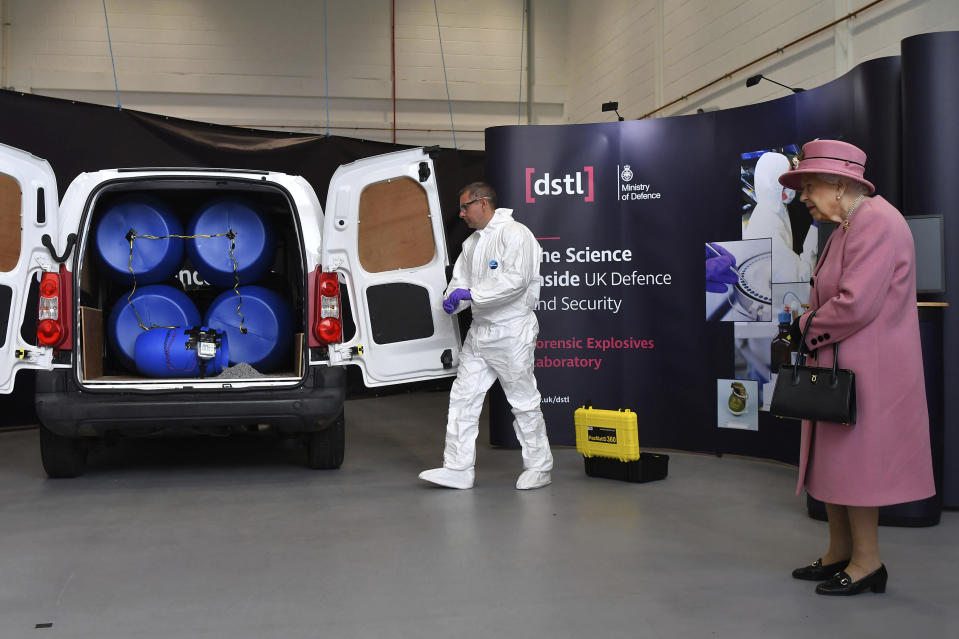 Britain's Queen Elizabeth II views a demonstration of a Forensic Explosives Investigation, with a model explosive device in a vehicle, during a visit to the Defence Science and Technology Laboratory (DSTL) at Porton Down, England, Thursday Oct. 15, 2020, to view the Energetics Enclosure and display of weaponry and tactics used in counter intelligence. (Ben Stansall/Pool via AP)