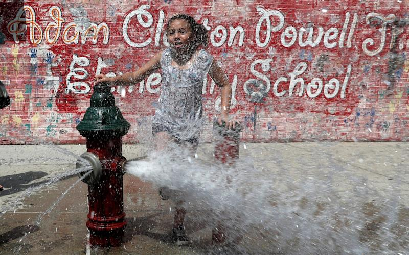 A girl cools off from the heat in New York City as extreme temperatures reach the East Coast - REUTERS