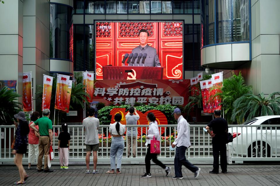 People watch a giant screen broadcasting Chinese President Xi Jinping's speech at the celebration marking the 100th founding anniversary of the Communist Party of China, in Shanghai, China July 1, 2021. REUTERS/Aly Song