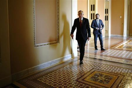 U.S. Senate Majority Leader Harry Reid (D-NV) (C) walks to address reporters after the weekly Republican caucus luncheon at the U.S. Capitol in Washington March 11, 2014. REUTERS/Jonathan Ernst