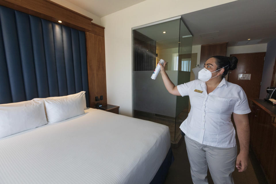Housekeeper sprays sanitizing spray in a room of the Costa Baja hotel on July 30, 2020 in La Paz, Mexico. (Photo by Alfredo Martinez/Getty Images)