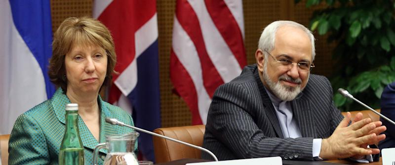 European Union foreign policy chief Catherine Ashton, left, and Iranian Foreign Minister Mohamad Javad Zarif, right, wait for the start of closed-door nuclear talks in Vienna, Austria, Tuesday, March 18, 2014. Ashton and Zarif have launched a new round of nuclear talks between Tehran and six world powers, putting a reported tiff behind them. The two sides hope to reach an agreement by July that trims Iran's nuclear activities in exchange for an end to sanctions choking Tehran's economy. (AP Photo/Ronald Zak)