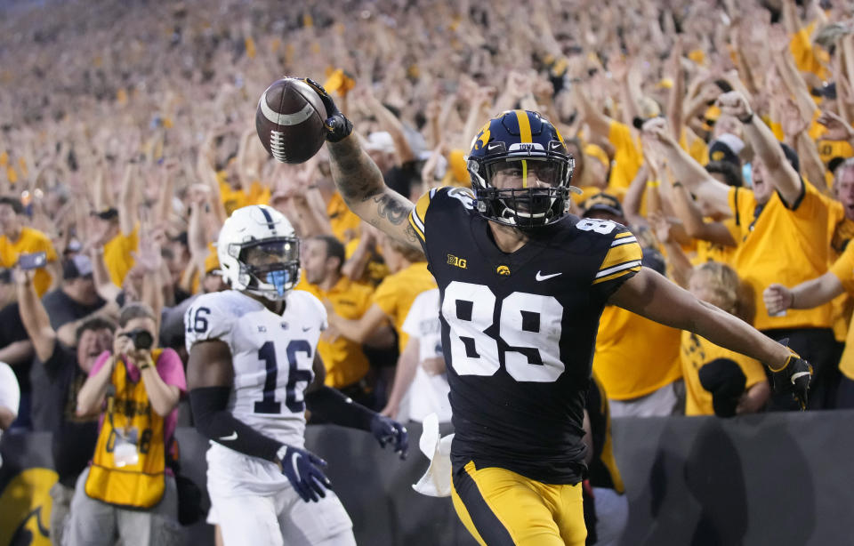 Iowa wide receiver Nico Ragaini (89) reacts after scoring a touchdown in front of Penn State safety Ji'Ayir Brown (16) during the second half of an NCAA college football game, Saturday, Oct. 9, 2021, in Iowa City, Iowa. Iowa won 23-20. (AP Photo/Matthew Putney)